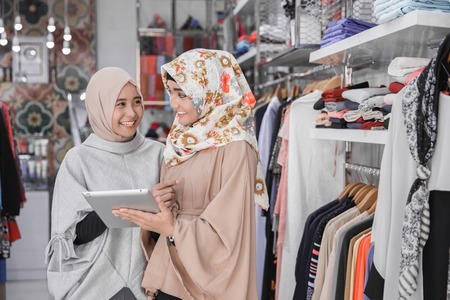 Portrait of a two young muslim business team with beautiful smile holding digital tablet while standing in their fashion boutique, female owner Stock Photo