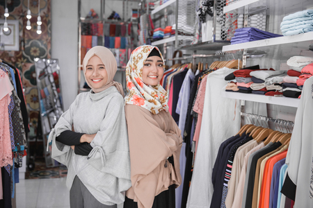 portrait of two attractive asian female business owner standing crossed arm in her boutique fashion store. muslim entrepreneur concept