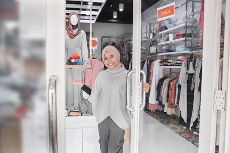 attraente donna musulmana asiatica lavoratore accoglienza clienti al suo negozio di moda boutique Archivio Fotografico