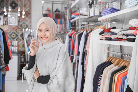 Beautiful asian muslim young woman using her smart phone with smile while standing at the clothing store Stock Photo