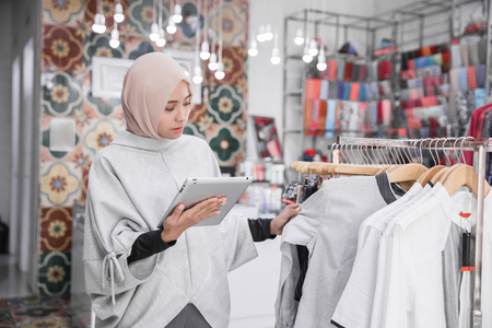 Portrait of a young muslim businesswoman with beautiful smile holding digital tablet checking stock in her fashion boutique, female owner Stock Photo