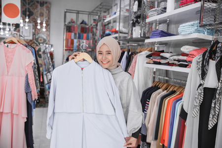 Beautiful excited muslim females with head scarf looking at blouse in fashion store