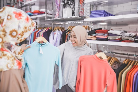 two happy female muslim best friend at fashion store