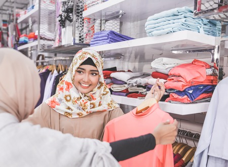 two happy female muslim best friend at fashion store. looking for opinion