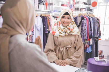 happy female cashier worker greeting customer in  fashion store Stock Photo