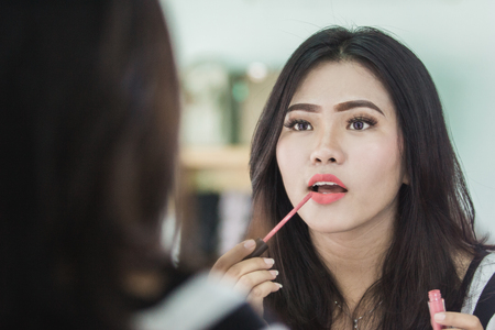 portrait of beautiful asian woman applying lipstick in make up room