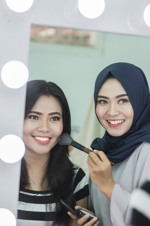 Make-up artist applying powder with a brush on models cheeks