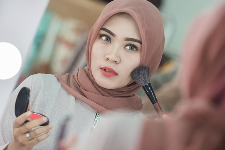 Beauty muslim woman with hijab applying makeup. Beautiful girl looking in the mirror and applying cosmetic. Girl gets blush on the cheekbones Stock Photo