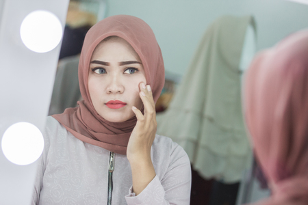 unhappy muslim woman with hijab looking at her face in the mirror Stock Photo