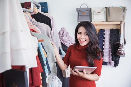Starting new business. Beautiful young asian woman using digital tablet smiling while standing at the clothing store
