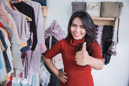 portrait of proud small fashion store owner smiling in her shop and showing thumb up