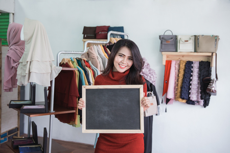 portrait of fashion store owner smiling while holding blank board sign in her shop Stock Photo