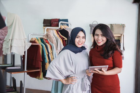 portrait of fashion shop owner and her assistant using tablet in fashion store Stock Photo