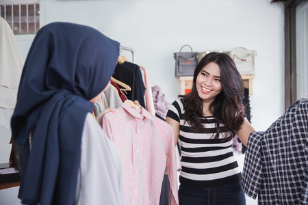 Attractive young woman choosing a new shirt at the clothing store with the help of a shop assistant Stock Photo