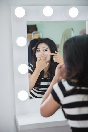 Acne treatment. Acne woman. Young woman squeezing her pimple, removing pimple from her face Stock Photo