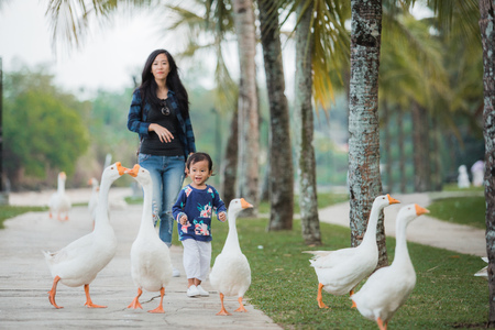 daughter and mother enjoy playing with goose