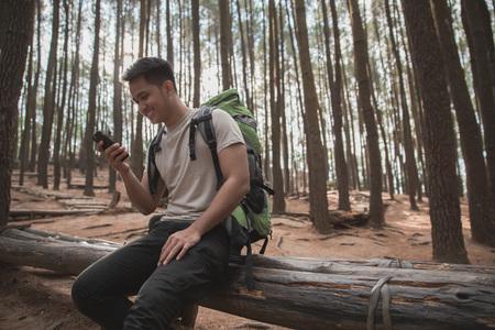 male hiker take a break and using mobile phone Archivio Fotografico