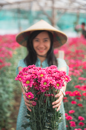 young asian woman showing chamomile flowers