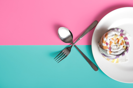 white plate with napkin, fork, and spoon on pastel background
