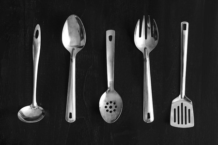 top view portrait of set of metal kitchen utensils on black wooden table