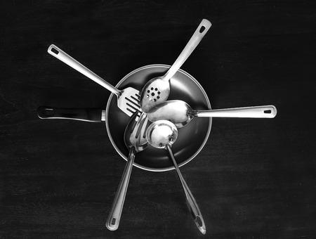 top view portrait of set of metal kitchen utensils and frying pan
