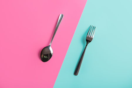 metal spoon and fork on pastel background Stock Photo