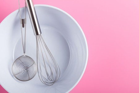 top view portrait of whisk egg and strainer in white bowl on pink background