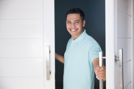 man open his front house door and smiling