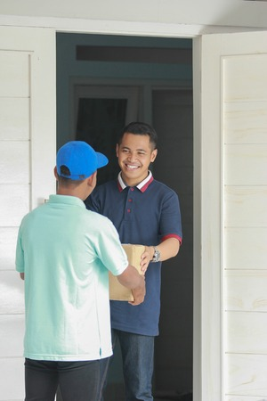 happy asian male receiving package Stock Photo