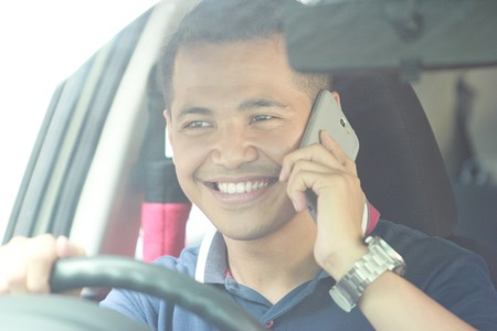 man using mobile phone while driving his car