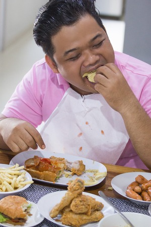 Young fat man eating Banque d'images - 96653497