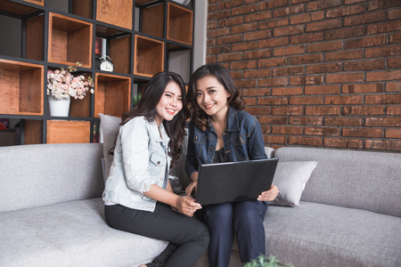 Two female friends activity using laptop Stock Photo