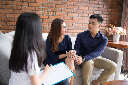 Young asian happy couple consulting with doctor Stock Photo