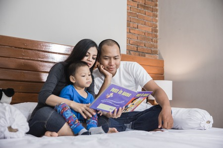 boy reading bed time story with parent