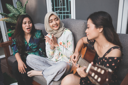 portrait of young asian woman playing guitar with friends