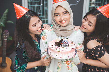 portrait of happy young asian woman celebrating birthday of her best friend Imagens