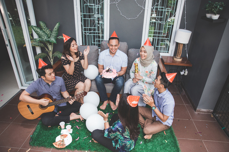 Group of friends enjoying brithday party and singing together