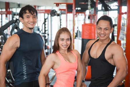 Three young people posing in gym