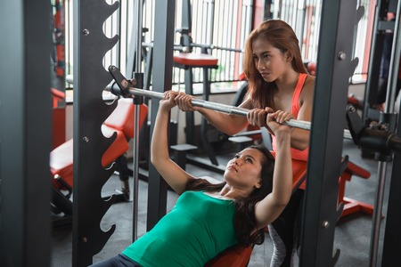 Young woman doing bench press