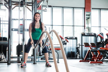 Fitness woman workout with battle rope