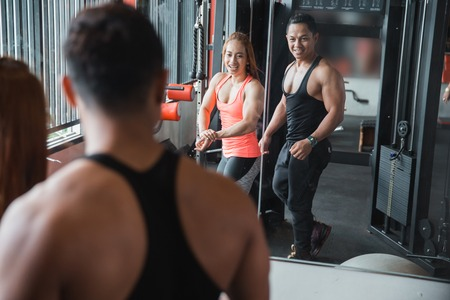 Muscular man and woman pose in front of the mirror at a gym