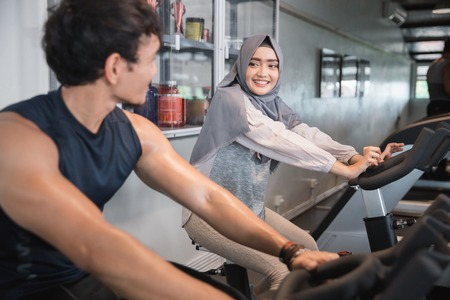 Muslim woman hijab and friend at the gym doing cardio exercises