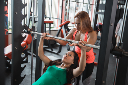 Woman working out with a barbell Stock Photo