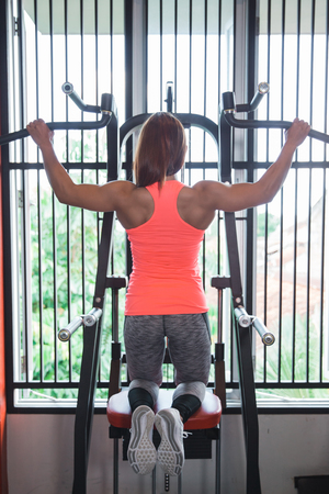 Woman exercising and doing pull ups Stock Photo