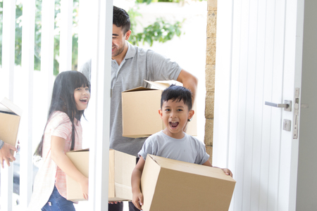 parent and kids with cardboard box. moving to new house Standard-Bild - 101144168