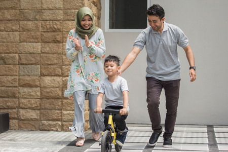 孩子与他的父亲学习如何骑自行车