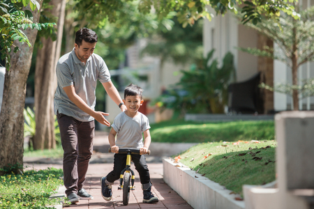 kids ride bicycle push by his father