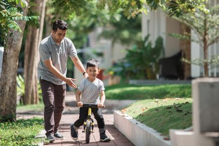 kinderen rijden fietsduw door zijn vader Stockfoto