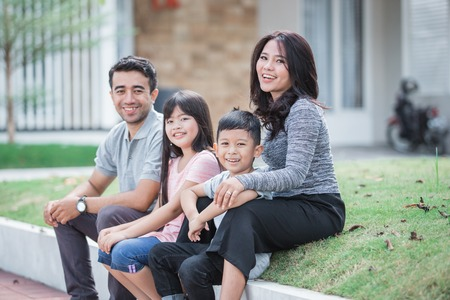 happy asian family in front of their house