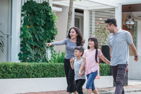 young happy asian family walking together
